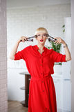 Emotional woman in a red dress with makeup brushes in their hand Royalty Free Stock Photos
