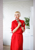 Emotional woman in a red dress with makeup brushes in their hand Royalty Free Stock Photo