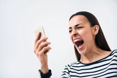 Emotional woman  standing  on white background. On the edge of fury.  Emotional bad tempered  cheerless woman holding cell phone and screaming while standing  on Stock Images
