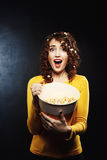 Emotional woman watching horror movie and looks scared sreaming loudly. Holding big bucket of popcorn Stock Photos
