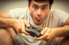 Emotional young addicted man playing video games. In living room Royalty Free Stock Photos
