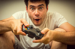 Emotional young addicted man playing video games Stock Photography
