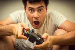 Emotional young addicted man playing video games. In living room Stock Photos