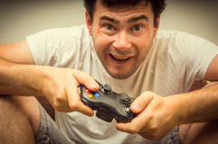 Emotional young addicted man playing video games. In living room Royalty Free Stock Photo