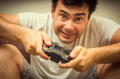 Emotional young addicted man playing video games. In living room Royalty Free Stock Image