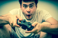 Emotional young addicted man playing video games. In living room - retro style Stock Photo