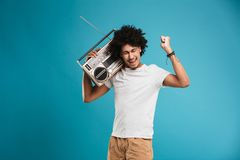 Emotional young african curly man holding boombox make winner gesture. Image of emotional young african curly man standing isolated over blue background holding royalty free stock image