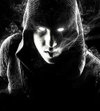 Emotional, young and attractive assassin on the black background. Stock Images