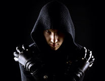 Emotional, young and attractive assassin in gloves on the black background. He is holding his hand on his shoulders. Serious face stock image