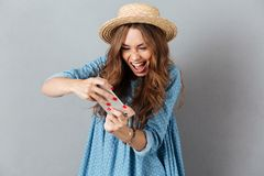 Emotional young caucasian woman play games by phone Royalty Free Stock Photo