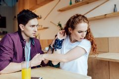 Young couple quarreling. Emotional young couple quarreling while sitting at table in cafe Stock Photo