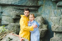 emotional young couple in raincoats terrified royalty free stock images