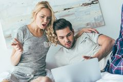 emotional young couple using laptop together stock photography