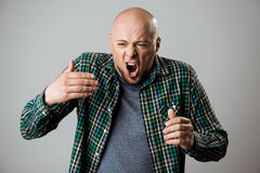 Emotional young handsome man shouting over beige background. Royalty Free Stock Photo