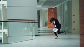 Emotional young lady businesswoman is dancing in hall of business center holding documents and to-go coffee enjoying stock footage