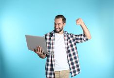 Emotional young man with laptop celebrating victory. On color background royalty free stock photos