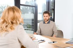 emotional young man looking at psychologist during stock images