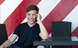 Emotional young man talking on the phone Stock Photos