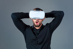 Emotional young man using a VR headset and experiencing virtual reality on grey background. A man dressed in a black shirt Stock Image