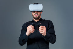 Emotional young man using a VR headset and experiencing virtual reality on grey background. A man dressed in a black shirt Royalty Free Stock Photography