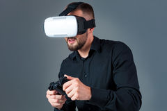 Emotional young man using a VR headset and experiencing virtual reality on grey background. A man dressed in a black shirt Stock Photography