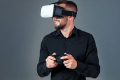 Emotional young man using a VR headset and experiencing virtual reality on grey background. A man dressed in a black shirt Royalty Free Stock Images