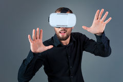 Emotional young man using a VR headset and experiencing virtual reality on grey background. A man dressed in a black shirt Stock Images