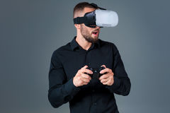 Emotional young man using a VR headset and experiencing virtual reality on grey background. A man dressed in a black shirt Royalty Free Stock Photos