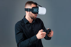 Emotional young man using a VR headset and experiencing virtual reality on grey background. A man dressed in a black shirt Stock Photo