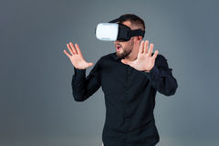 Emotional young man using a VR headset and experiencing virtual reality on grey background. A man dressed in a black shirt Stock Photos