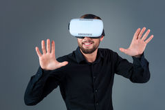 Emotional young man using a VR headset and experiencing virtual reality on grey background. A man dressed in a black shirt Royalty Free Stock Photo