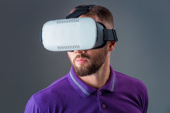 Emotional young man using a VR headset and experiencing virtual reality on grey background. A man dressed in a purple T-shirt Royalty Free Stock Photo