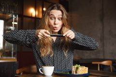 Emotional young pretty woman sitting in cafe indoors take a photo of her breakfast by mobile phone royalty free stock images