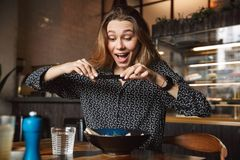 Emotional young pretty woman sitting in cafe indoors take a photo of her breakfast by mobile phone royalty free stock image