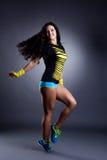 Emotional young sportswoman dancing in studio Stock Images