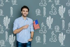Emotional young tourist smiling and holding a flag of the USA stock photos