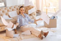 Emotional young woman celebrating her promotion at work. Joyful day. Cheerful excited young woman looking happy while sitting on the floor with documents falling Stock Image