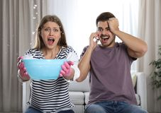Emotional young woman collecting water leaking from ceiling while her husband calling plumber stock photography