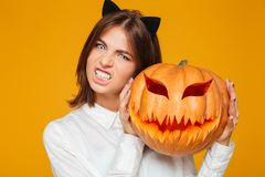 Emotional young woman dressed in crazy cat halloween costume. Picture of emotional young woman dressed in crazy cat halloween costume over yellow background with royalty free stock images