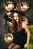 Happy gothic young woman in witch halloween costume with hat sitting at chair stock images