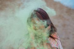 Emotional young woman having fun in a cloud of green dry paint, celebrating Holi colors festival at the desert stock images