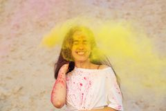 Emotional young model having fun in a cloud of yellow dry powder, celebrating Holi colors festival at the desert stock image