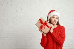 Emotional Young Woman In Santa Hat With Christmas Gift Near White Brick Wall Stock Photos