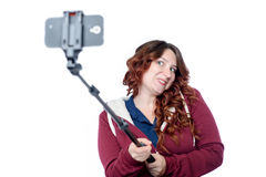 Emotional young woman making selfie with a stick on white Royalty Free Stock Image