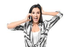 Emotional young woman speaking by mobile phone. On white background Royalty Free Stock Photography