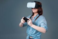 Emotional young woman using a VR headset and experiencing virtual reality on grey background Royalty Free Stock Photos