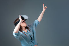 Emotional young woman using a VR headset and experiencing virtual reality on grey background Stock Image