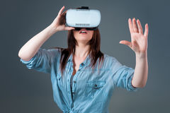 Emotional young woman using a VR headset and experiencing virtual reality on grey background. A woman dressed in a denim shirt Royalty Free Stock Photo
