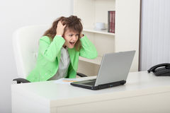Emotional young woman on workplace with laptop Royalty Free Stock Photography