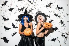 Emotional young women in halloween costumes. Royalty Free Stock Images